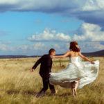 Glückliches Hochzeitspaar nach der Trauung im Freien, springend auf einem Feld