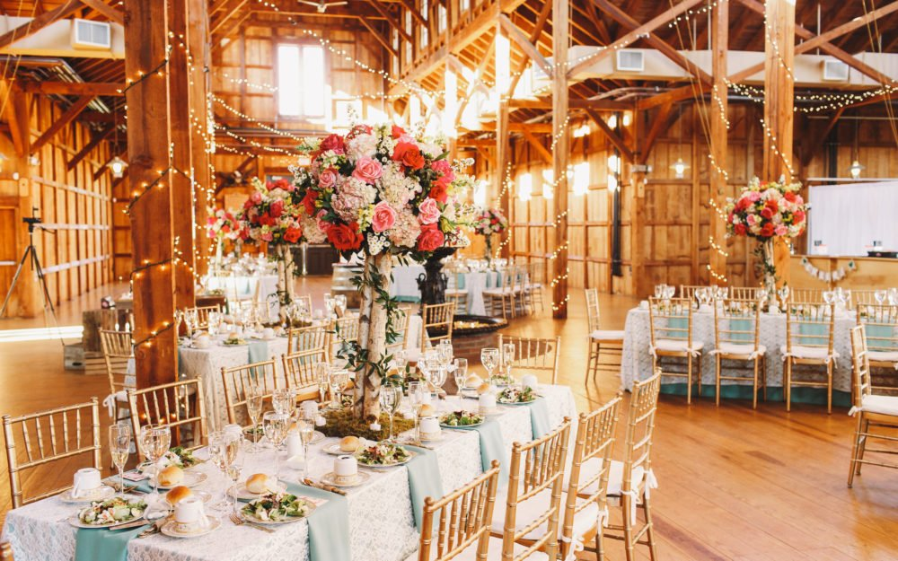 Gedeckte und schön dekorierte Tafeln, angerichtet in einer Scheune mit hohen Blumensträussen