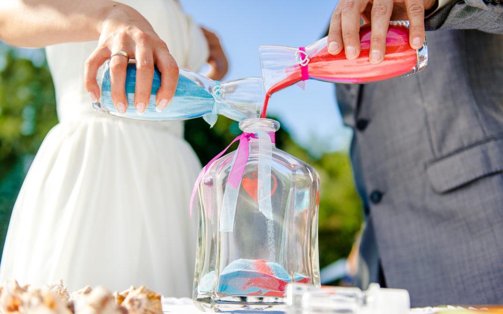 Brautpaar gießt verschieden farbigen Sand in eine Glasflasche als Zeremonie zur Hochzeit