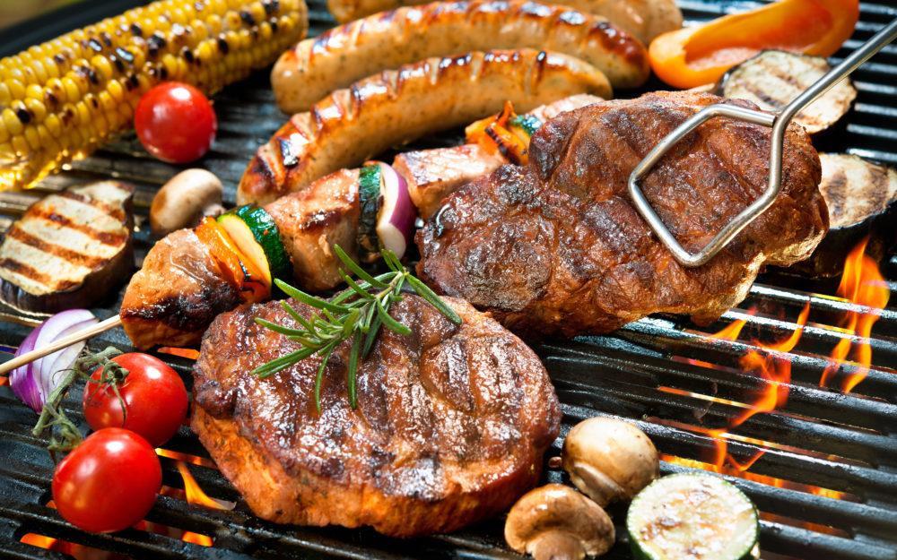 Grill auf dem Steak, Hähnchenspieße und Gemüse über einem Feuer gegrillt werden
