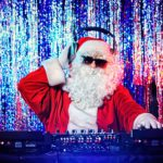 DJ als Weihnachtsmann verkleidet mit Sonnenbrille auf einer Weihnachtsfeier