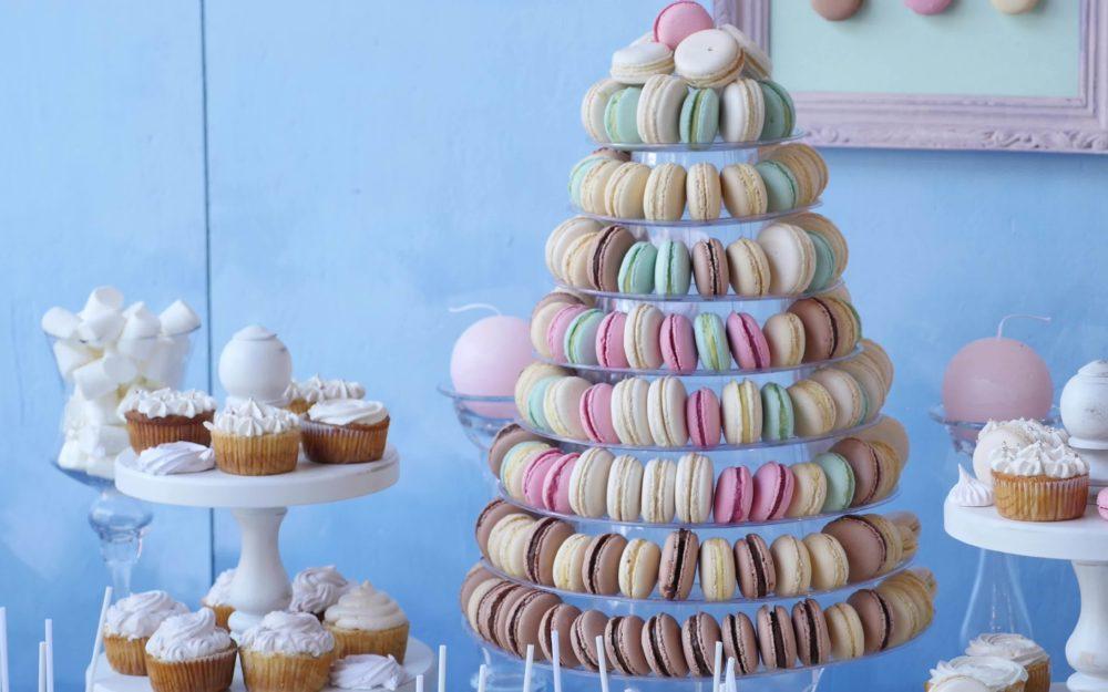 Buffet aus leckeren Macarons und Cupcakes ins Pastellfarben vor einer blauen Wand