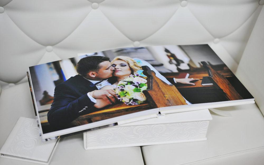 Aufgeschlagenes Fotobuch mit Hochzeitsfoto auf einer weißen Schachtel auf einer weißen Ledergarnitur