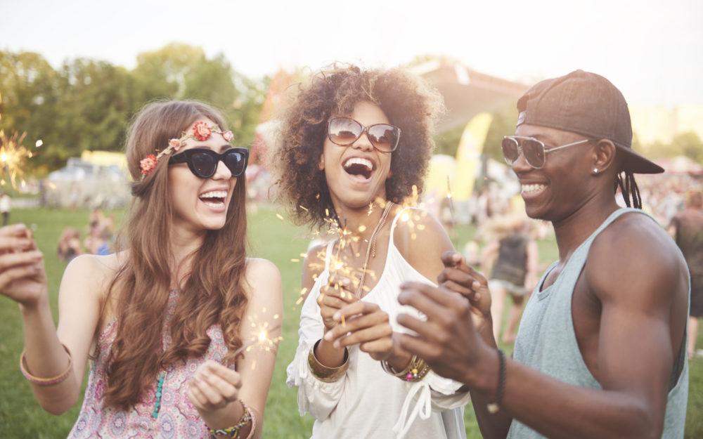Drei Freunde feiern mit Wunderkerzen auf einem Open Air Fest