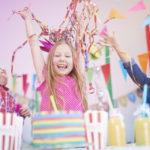 Kinder feiern mit Deko-Papierschlangen und Wimpeln Kindergeburtstag