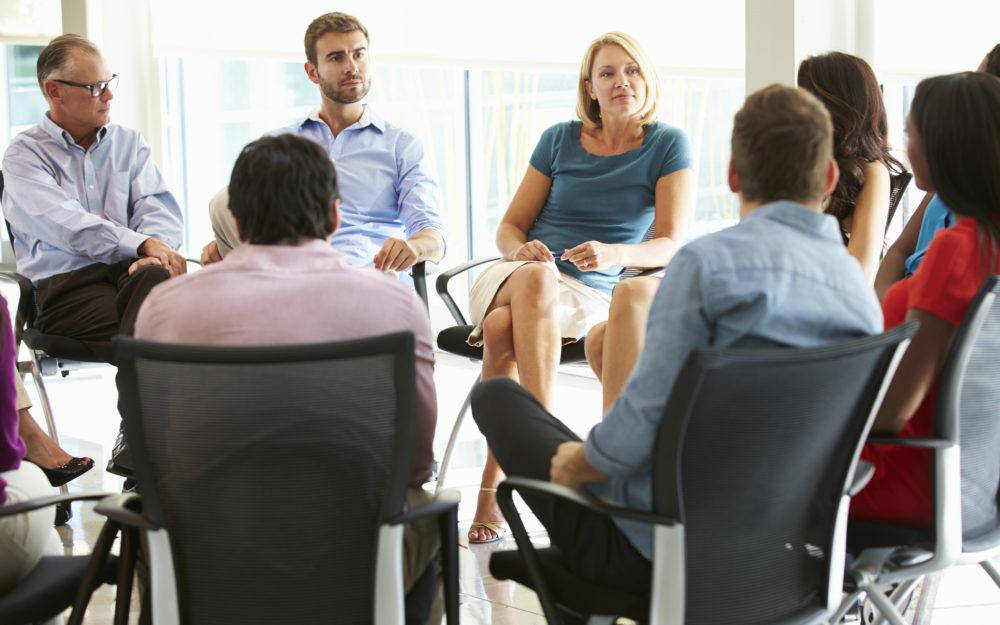 Menschen sitzen in einem Stuhlkreis und besprechen etwas