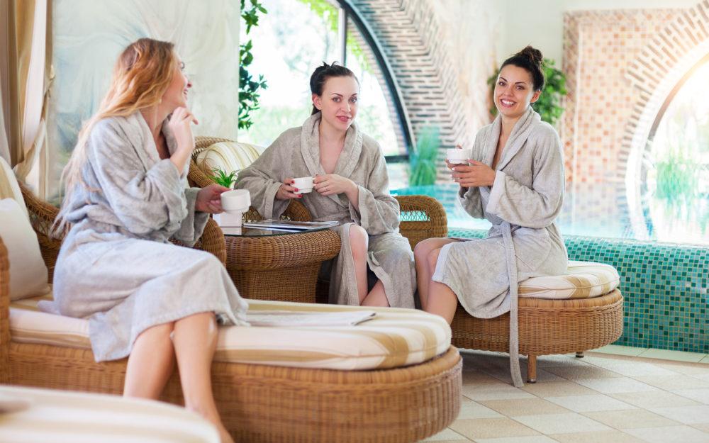 Drei Frauen entspannend im Wellnessbereich mit Kaffeetassen in der Hand
