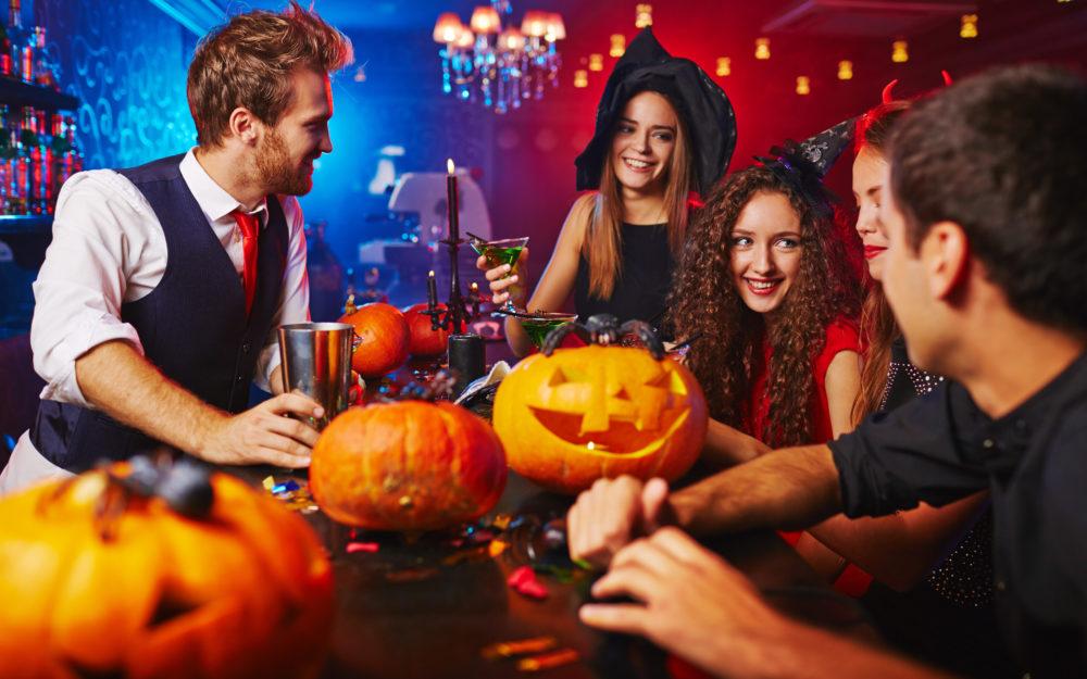Halloween Party von Freunden in einer Bar mit Deko-Kürbissen auf dem Tresen