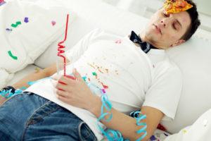 Betrunkener junger Mann liegt auf dem Rücken nach einer Party