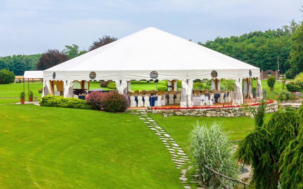 Ein großes Zelt auf einer grünen Wiese mit einer Gala-Bestuhlung als Festzelt.