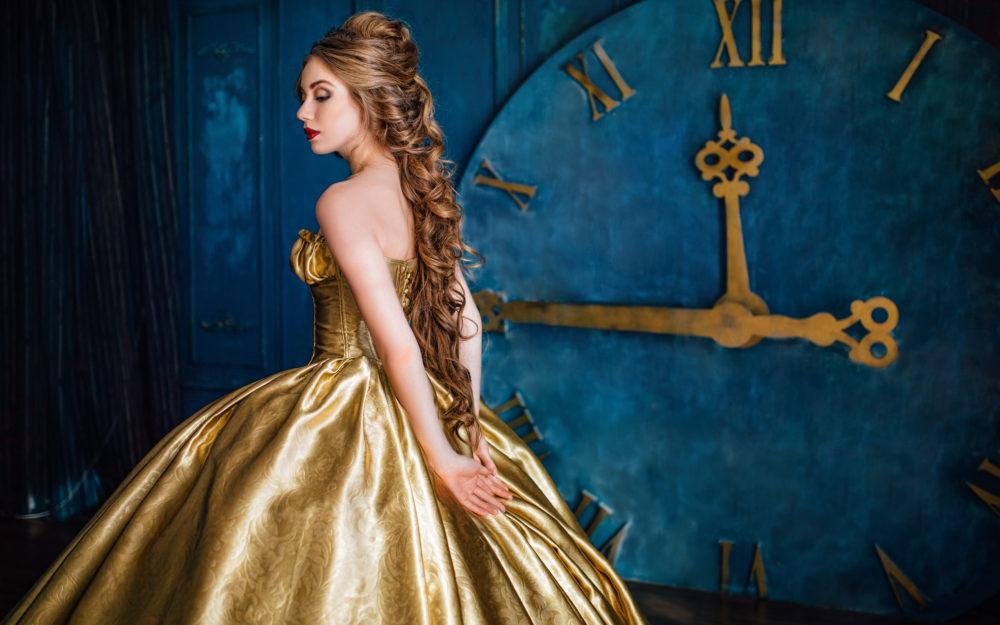 Junge Frau in goldenem, weiten Kleid vor einer riesigen Uhr, die auf Viertel vor Zwölf steht