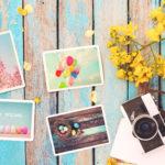 Fotokarten mit Frühlingsmotiven auf einem pastellfarbenen Tisch mit Kamera und gelben Blumenblüten