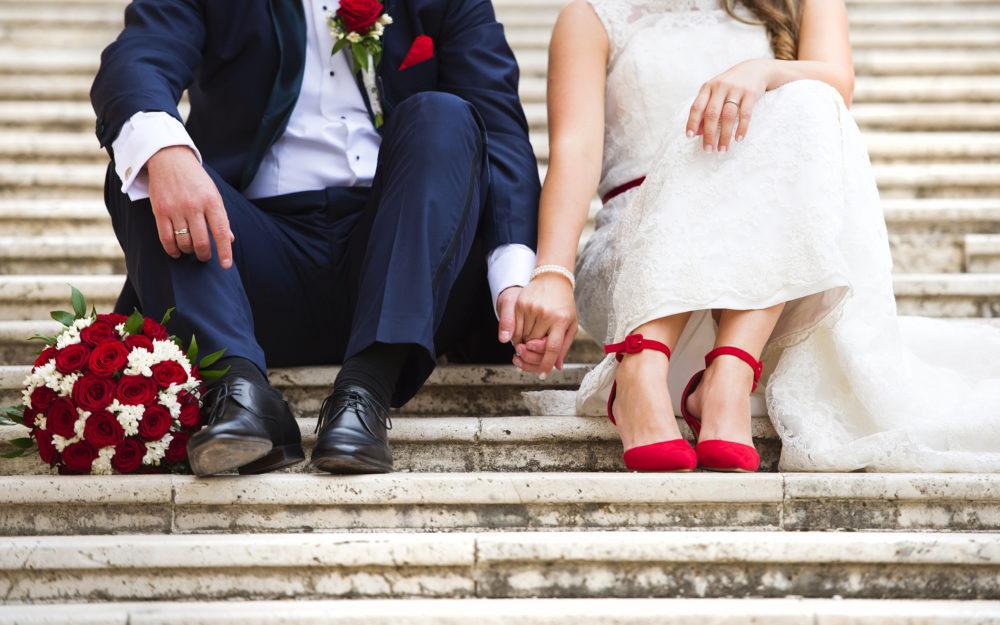 Brautpaar sitzend auf einer Stein-Treppe mit Brautstrauß und Eheringen