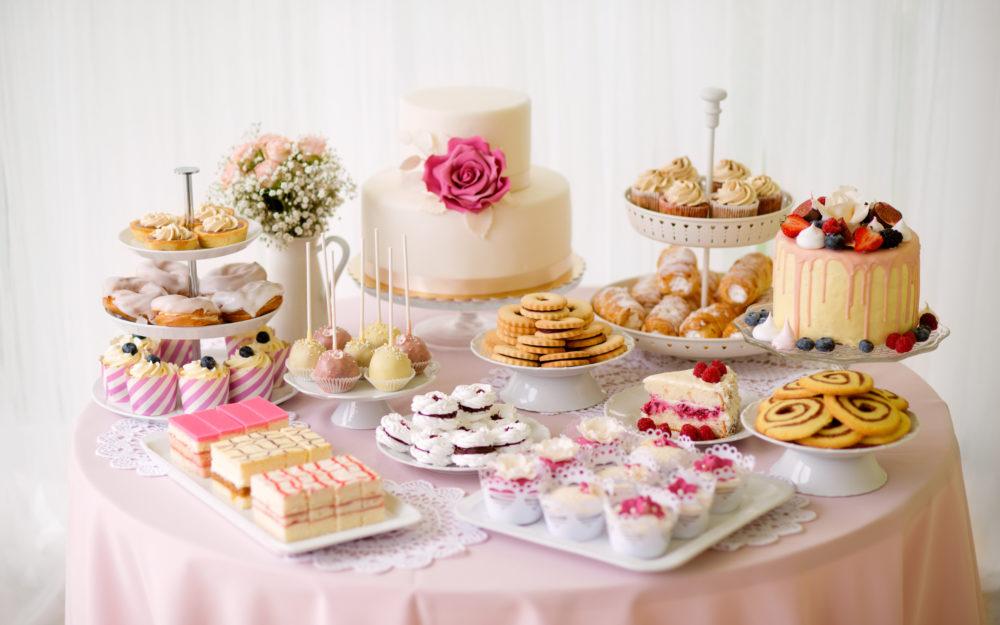 Verschiedene Süßspeisen als Buffet angerichtet auf einem runden Tisch in Rosa und Weiß