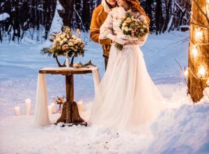 Hochzeitspaar im Schnee im Freien mit winterlicher Dekoration und weißem Brautkleid