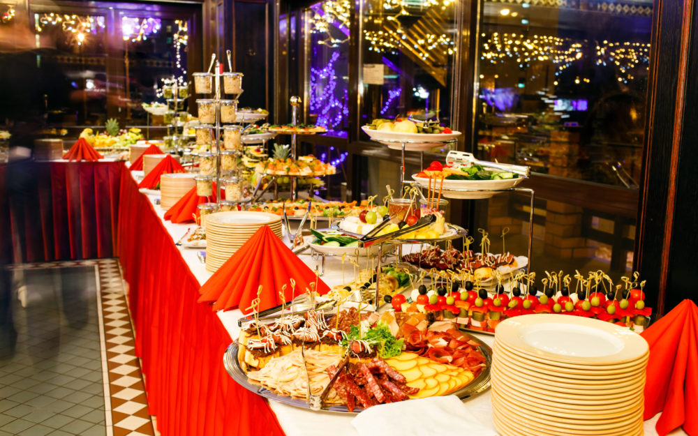 Ein Buffet mit roter Tischdecke, leckeren Speisen weihnachtlich geschmückt zur Weihnachtsfeier