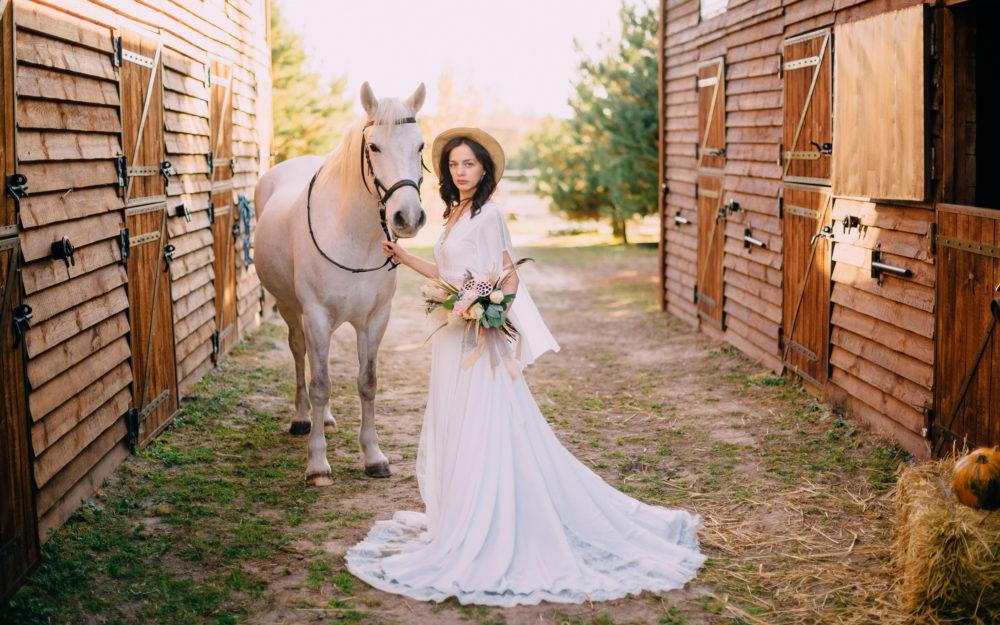 Eine geschmückte Braut posiert neben einem weißen Schimmel vor einem Pferdestahl
