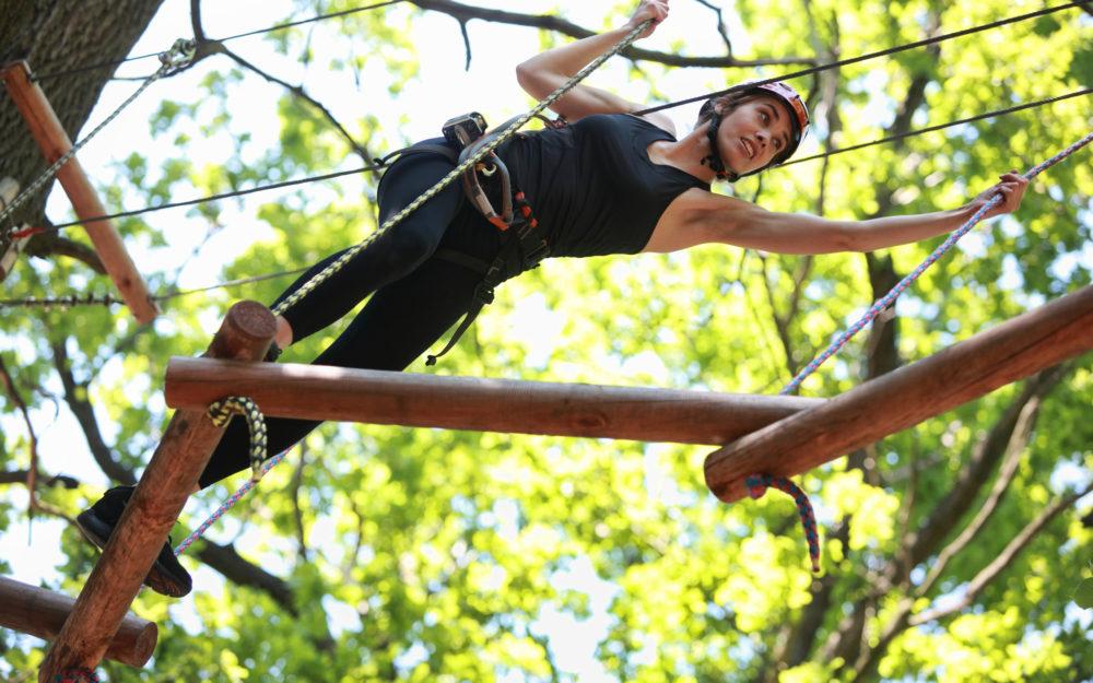 Frau klettert an Seilen durch einen Parcour in den Bäumen