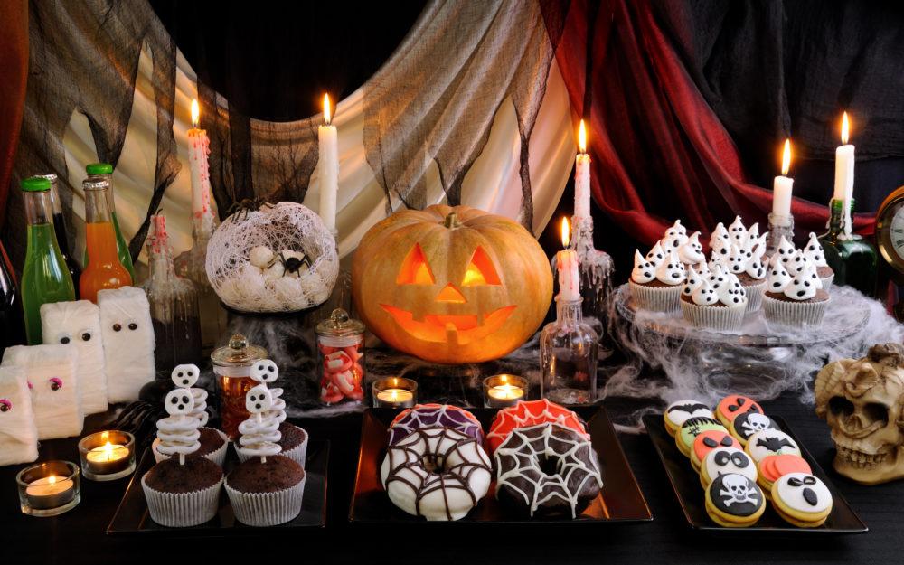 Geschmückter Halloween Tisch als Halloween Süßigkeiten-Buffet mit Kerzen