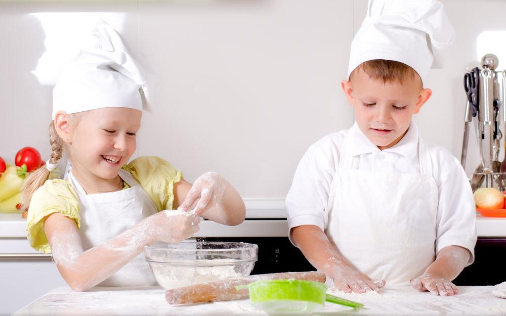 Zwei kleine Kinder in Kochschürze und Kochmütze in der Küche beim Backen