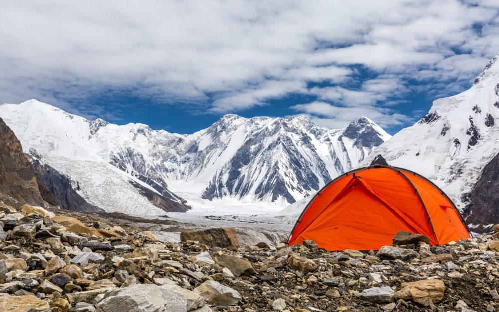 Ein rotes Zelt auf steinigem Boden auf einem Berg mit Gletschern im Hintergrund.