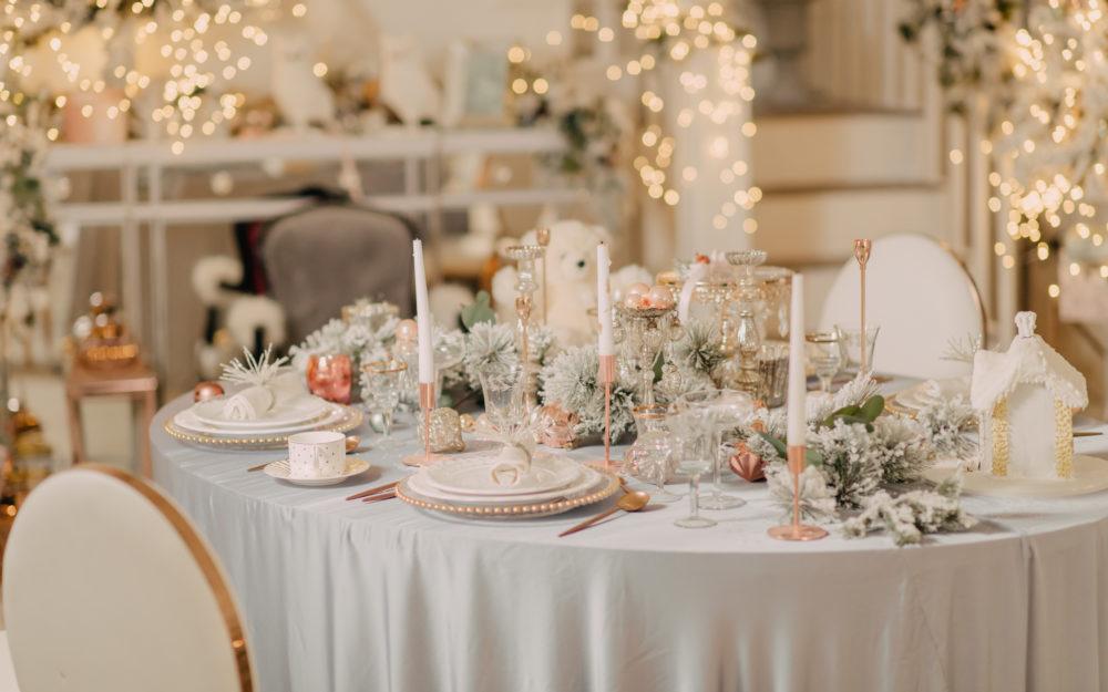 Gedeckter Hochzeitstisch in Weiß mit viel Dekoration und besonderem Licht in Weiß, Rosa und Gold