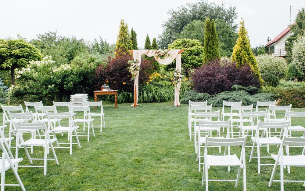 Blick auf die Kulisse einer Trauung mitten im grünen Garten mit weißen Holzstühlen
