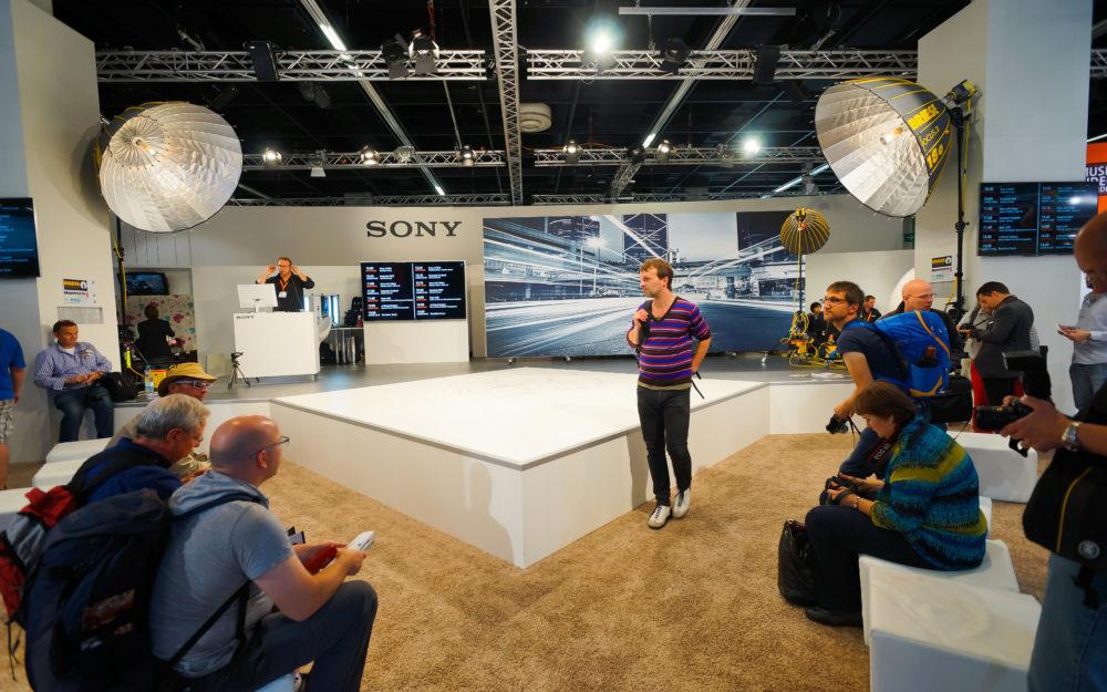 Eine Produktpräsentation vor Besuchern in einem Messeraum als Eventlocation mit zwei großen Licht-Strahlern