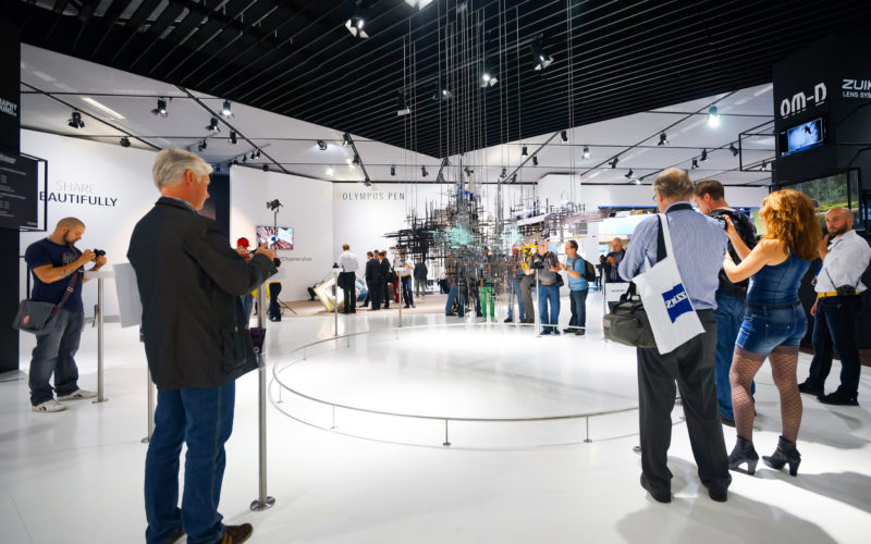 Eine Produktpräsentation während einer Messe mit weißer Dekoration und verschiedenen Besuchern