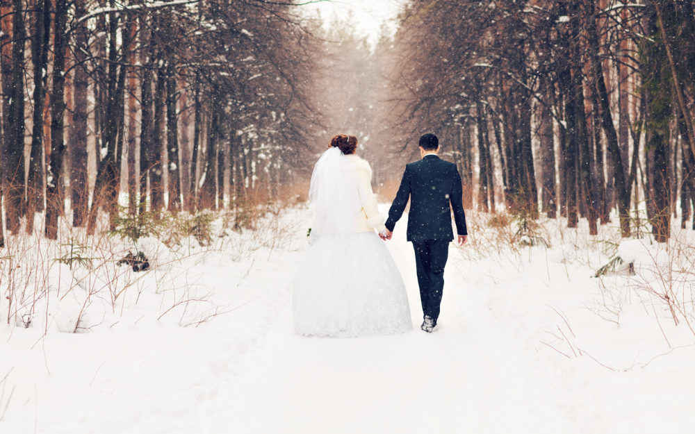 Romantisches Hochzeitspaar von hinten, Hand in Hand laufend im weißen Schnee, Open Air mitten im idyllischen Wald