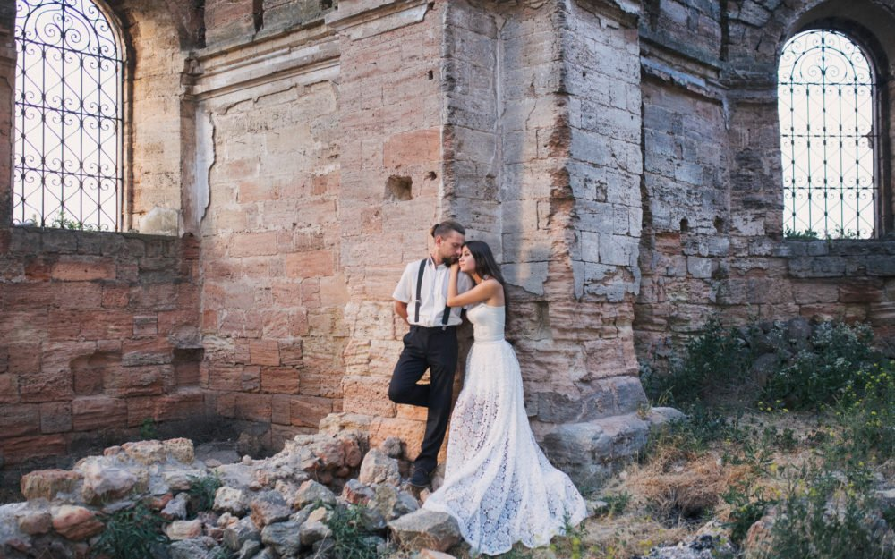 Brautpaar in einer verlassenen Ruine mit alten Stein und verschnörkelten Gittern vor den Fenstern
