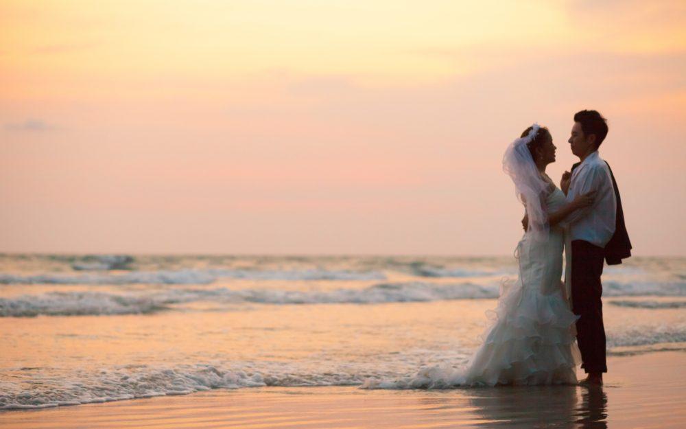 Blick auf ein Hochzeitspaar am Strand mit Meer und Wellen im Hintergrund während des Sonnenuntergangs