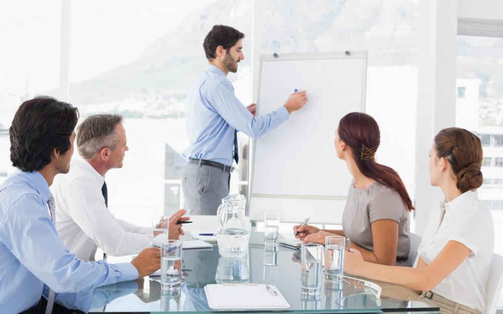 Ein Mann präsentiert etwas vor vier anderen in einem Büro