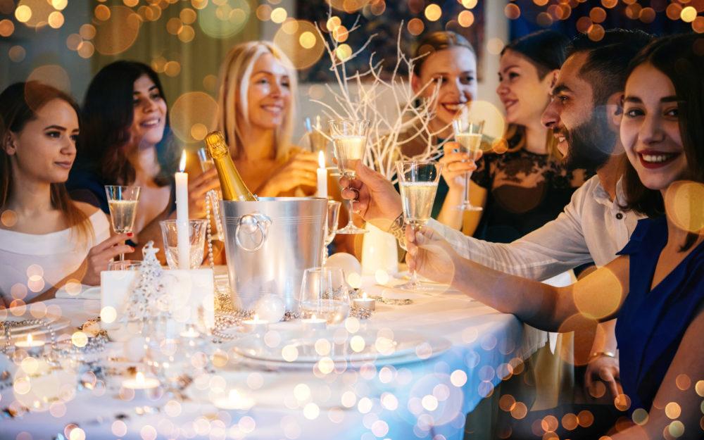 Feiernde Frauen an einer gedeckten Tafel mit Kerzen geschmückt zur Weihnachtsfeier