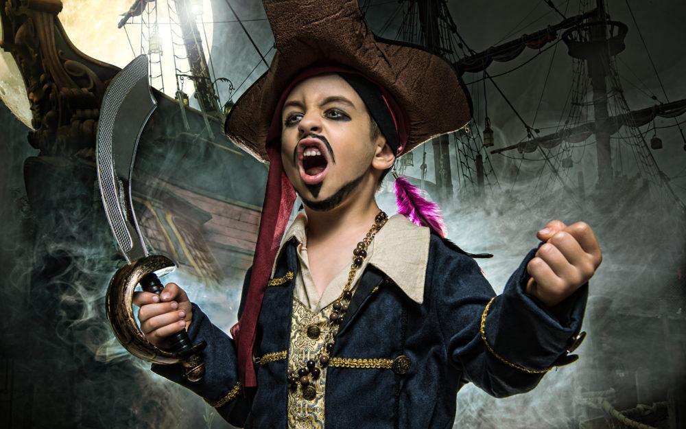 Ein Jugendlicher, verkleidet als Pirat mit Säbel in der Hand