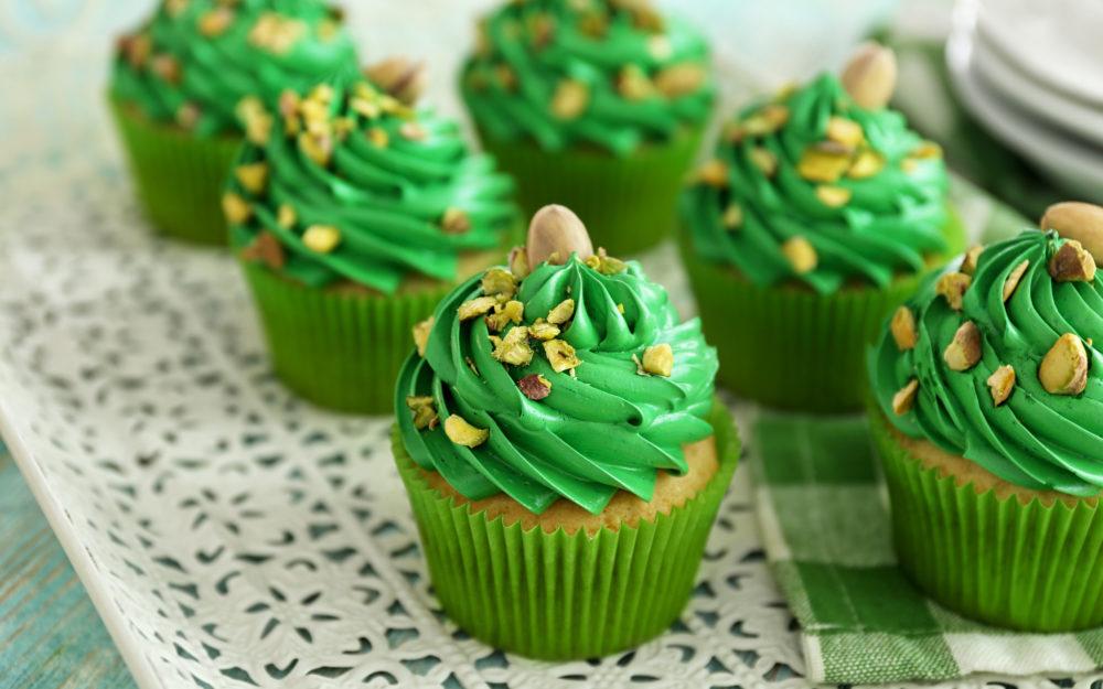Sechs Cupcakes auf einem Tisch angerichtet mit grünem Topping als Dekoration