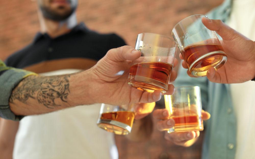 Vier Männer stoßen mit Gläsern gemeinsam an