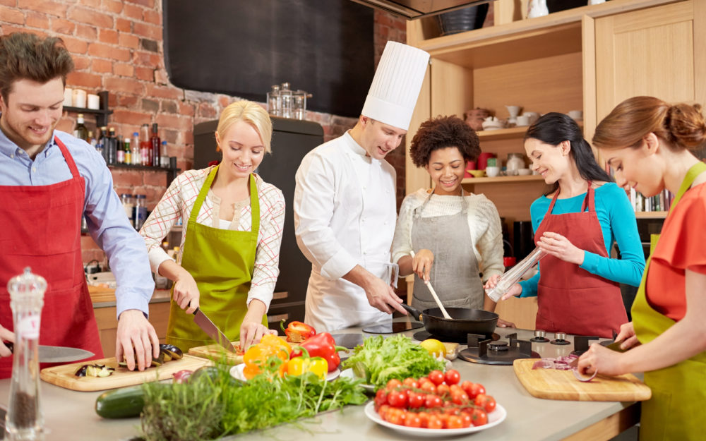 Kochevent mit fünf Personen und einem Koch in einer Küche, die Gemüse schneiden und gemeinsam Essen zubereiten