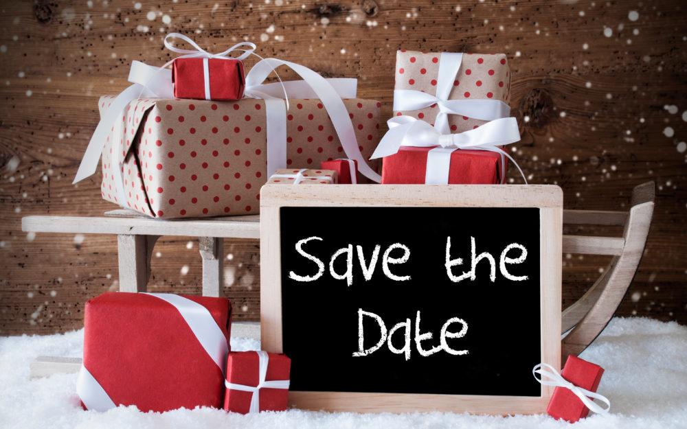 Holzschlitten im Schnee mit Geschenken und einer Save The Date Tafel