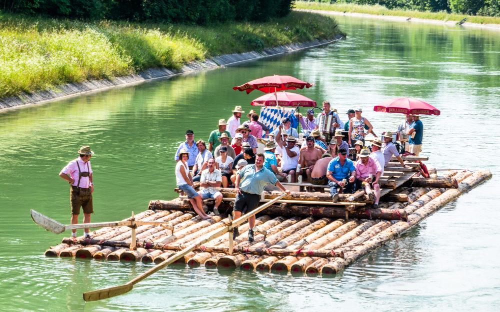 Ein großes Floß aus Baumstämmen mit einer Gruppe Menschen darauf als Teambuilding Maßnahme