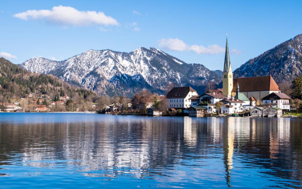 Herrlicher Blick vom Tegernsee auf eine Kirche in blauer Stimmung