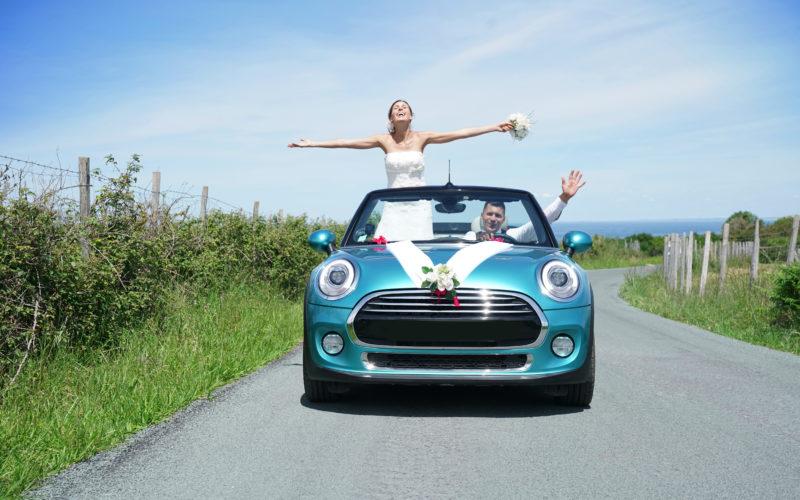 Hochzeitspaar in einem geschmückten Caprio Auto auf einer kleinen Landstraße bei Sonnenschein