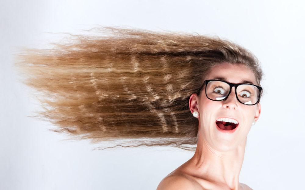Frau mit großen Augen und Brille und im Wind wehenden Haaren für frische Luft im Kopf beim Brainstorming