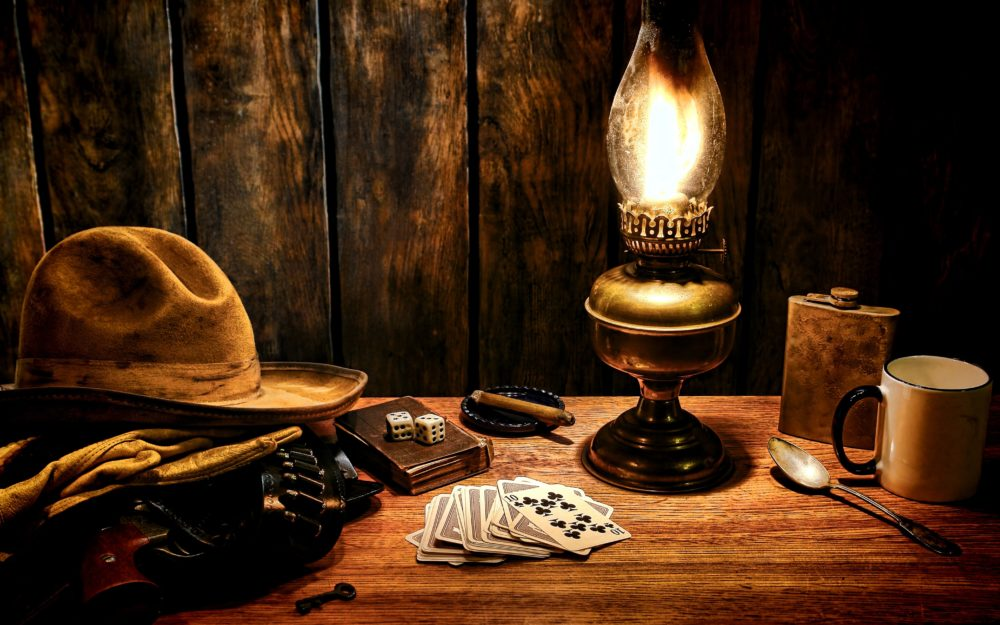Tisch mit verschiedenen Utensilien wie Karten, ein Löffel und ein Hut in düsterer Stimmung