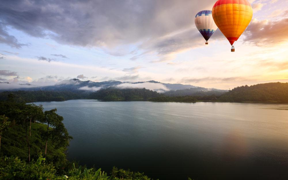 Blick auf einen See in der Abenddämmerung mit zwei Heißluftballons am Himmel