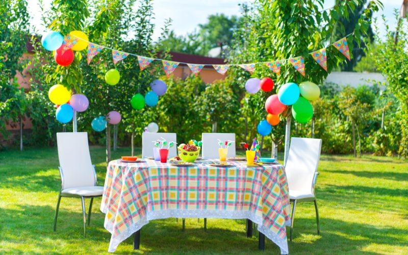 Gedeckter Tisch mit Dekoration aus Wimpeln und Luftballons zum Geburtstag auf einer grünen Wiese im Freien