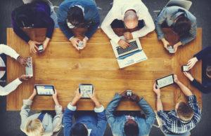 Menschen mit Laptops, Tablets und Smartphones sitzen um einen Tisch herum, Blick von oben