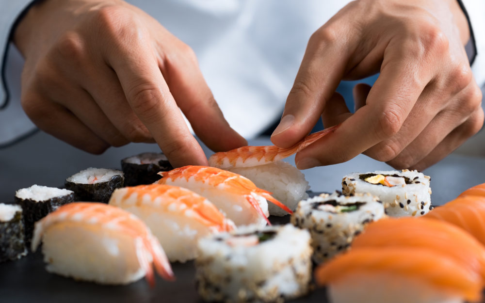Verschiedene Sushirollen auf einem Tisch, die gerade frisch zubereitet werden