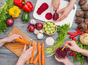 Gemüse wie Karotten und Rote Beete werden bei einem Kochevent auf einem Holztisch auf einem Brett geschnitten als Zutat für ein Essen