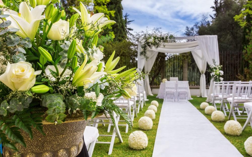 Hochzeitslocation für eine Trauung im Freien und im Grünen mit weißen Stühlen und romantischer Dekoration in Grün und Weiß